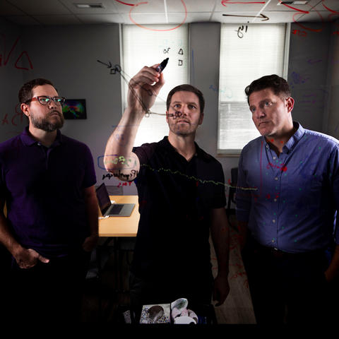 photo of UK neuroscientists looking at notes on a glass writing board