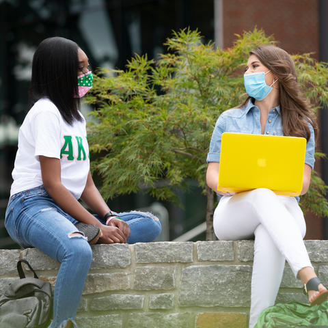 two female students wearing masks sitting on wall outside talking to each other
