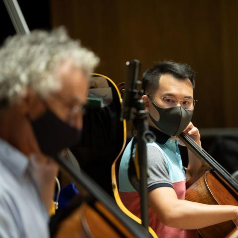 photo of masked Professor Benjamin Karp playing with 2 student musicians