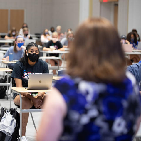 photo of journalism class with students in  masks and back of College of Communication and Information Dean Jennifer Greer's head as she speaks to them.