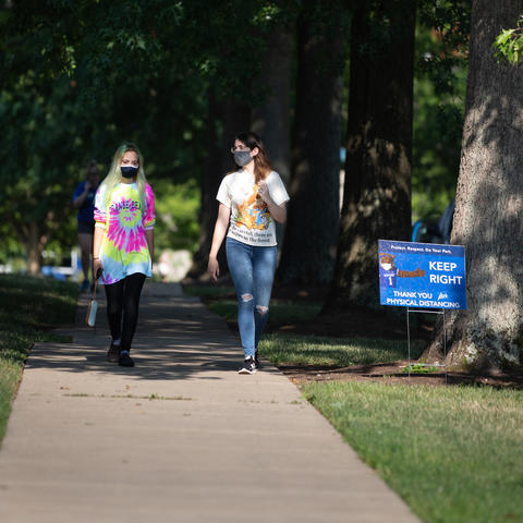 Image of two students walking on campus wearing face masks