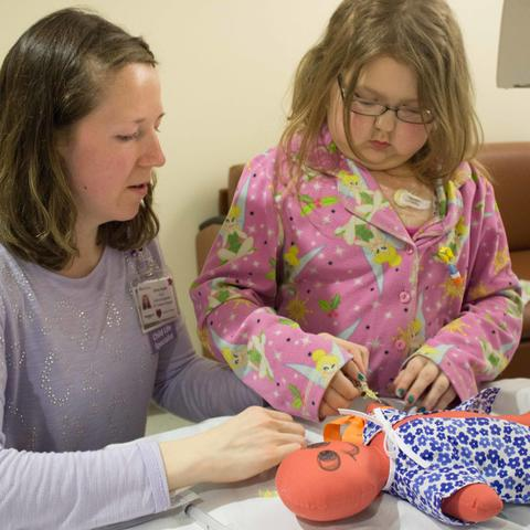 Child Life Specialist Ashley Rapske helps young Shannon understand how IVs work by practicing on a doll.
