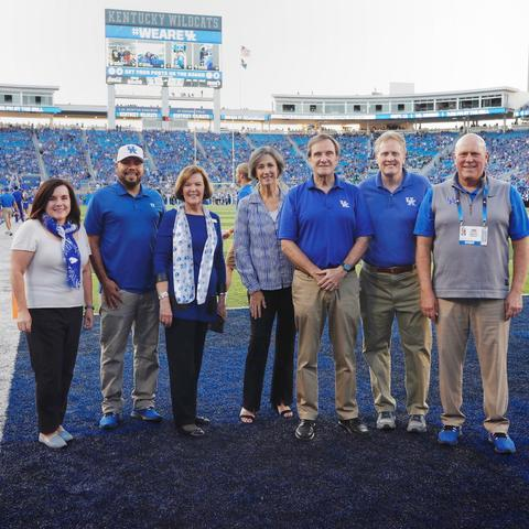 photo on Kroger Field of Jennifer Greer, Julian Vasquez Heilig, Rossetta Sandidge, Mary Davis, Jeffrey Okeson, Derek Lane, and Provost David Blackwell.