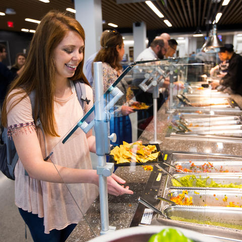 photo of young woman at a food buffet