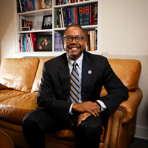 Dean Brennen seated in office on brown couch wearing suit and glasses