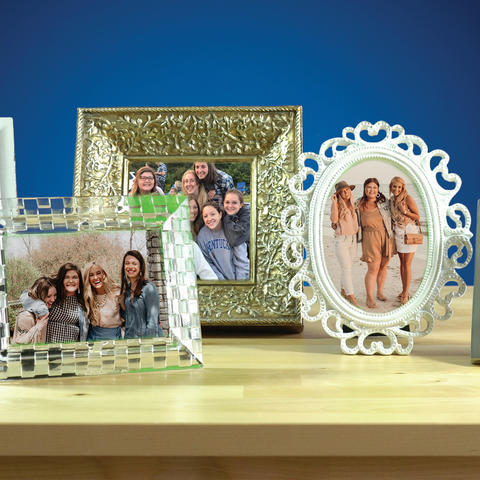Photo of several frames with photos in them sitting on a table