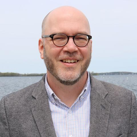 headshot photo of Doug Way in front of body of water