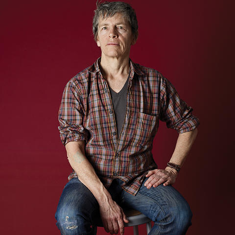 photo of Eileen Myles on stool with red background by Catherine Opie