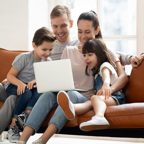 family sitting on sofa looking at laptop computer