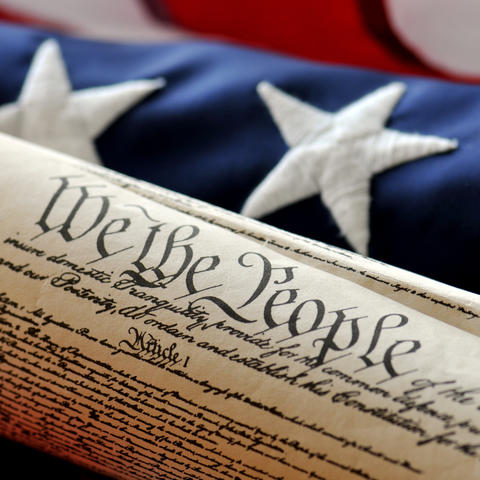 Image of U.S. Constitution in front of American flag