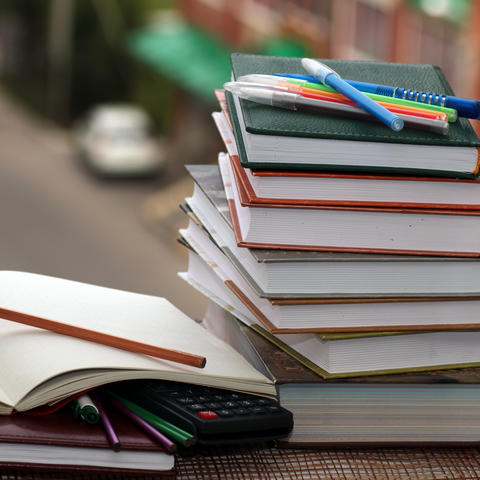 photo of a stack of books, a notebook and pens