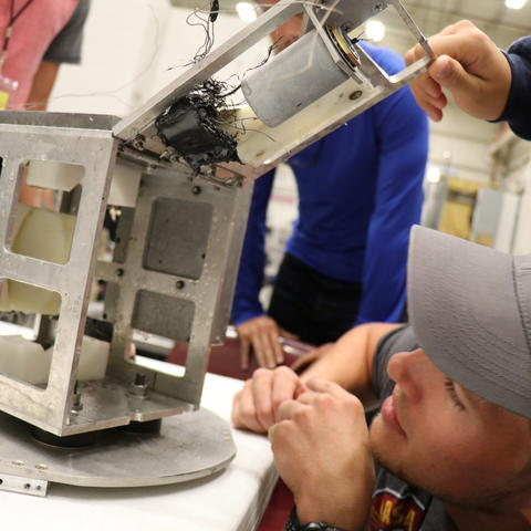 Photo of Devin Sparks examining the capsule ejection module after retrieval.
