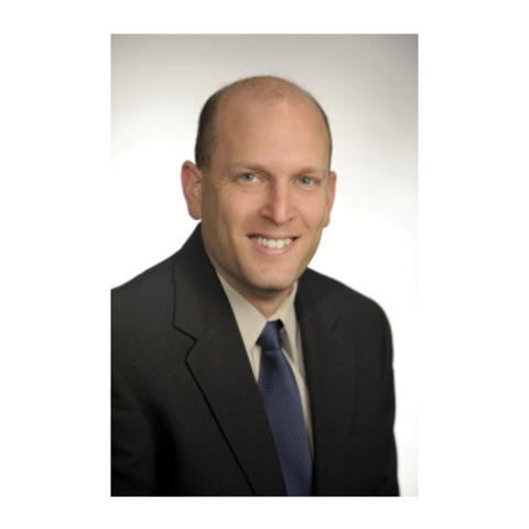 Joshua Douglas faculty portrait wearing a black suit with blue tie on white background