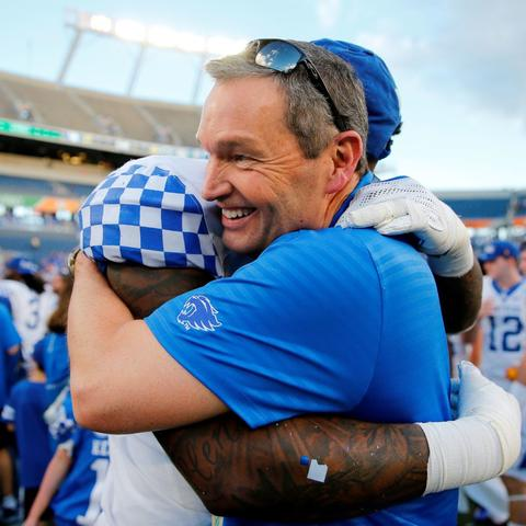 photo of Mitch Barnhart hugging UK football player after UK won the Citrus Bowl Jan. 1, 2019