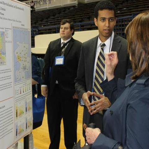 photo of male undergrad presenting research poster presentation to woman