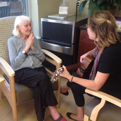 photo of patient listening to music therapist Meghan Ross play guitar at Oaknoll Retirement Residence in Iowa City
