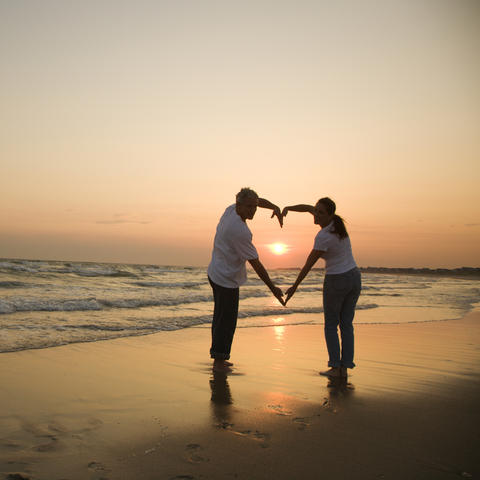 stock art photo of couple forming a heart with their arms on beach with sunset background