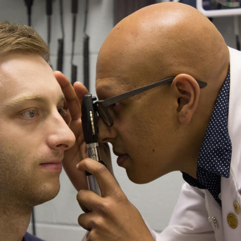 Paras Vora uses an ophthalmoscope to examine a male patient's eye