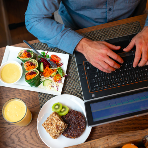 Man working at computer with food.