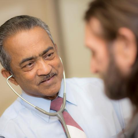 photo of Dr. Roy Varghese with a patient