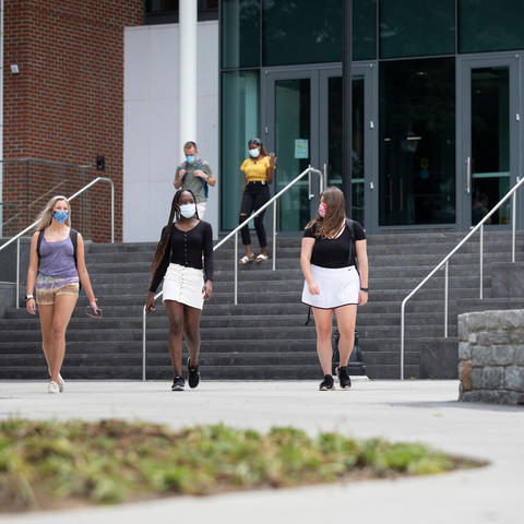 three students wearing masks for covid protection walking on campus