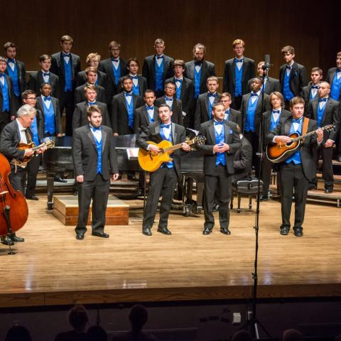 UK Men's Chorus on stage with group of instrumentalists