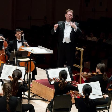 photo of John Nardolillo conducting members of UK Symphony Orchestra at Carnegie Hall