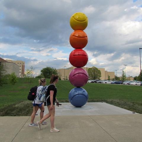 """photo of 2 students passing by """"Mood Sculpture"""" by Tony Tasset"""