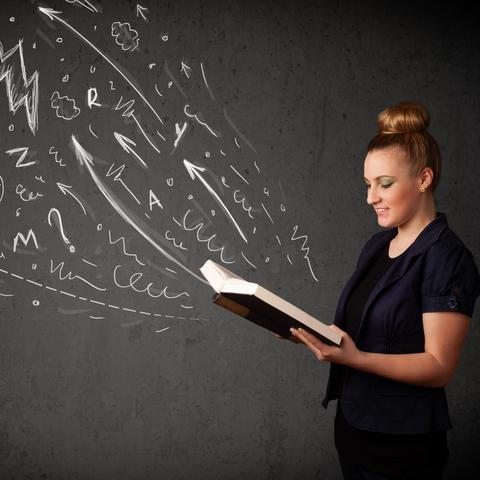 photo of woman with book open and drawings on chalkboard appearing to rise from it