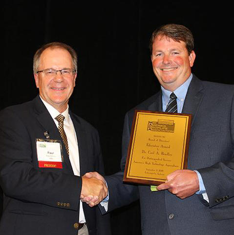 Carl Bradley in suit attire accepting his award in hand