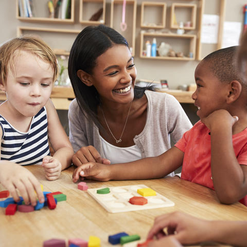 photo of teacher talking to children in child care setting