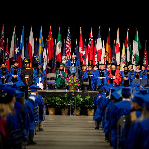 photo of December 2019 Commencement with flags on the platform where speakers and deans are sitting and President Capilouto at the podium