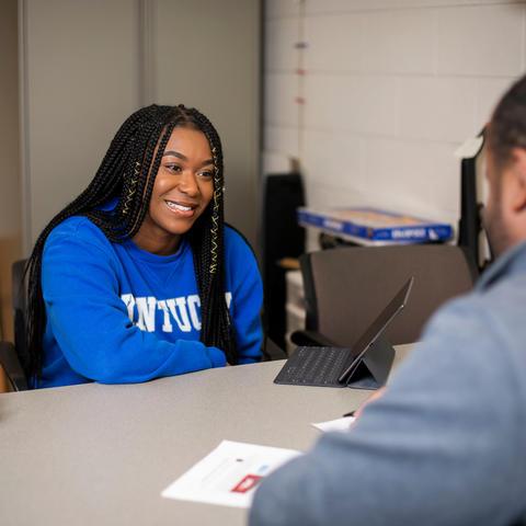 female student at desk talking to male advisor