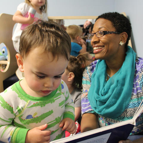 Stefani Whaley, a health and safety coach with Child Care Aware of Kentucky,  shares a book with a child during a technical assistance visit.