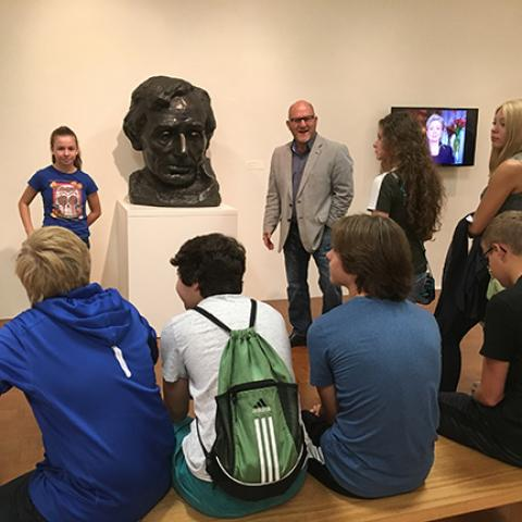 "Stuart Horodner, standing next to a bust of Abraham Lincoln by Gutzon Borgulm, leads high schoolers on ""POTUS"" tour"