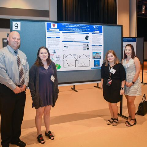 photo of teacher and students presenting research