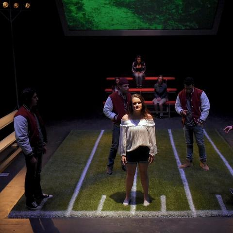 """photo of girl surrounded by 4 athletes from UK Theatre's """"Good Kids"""""""