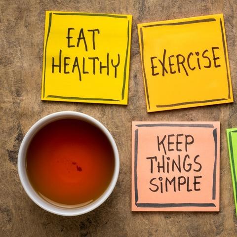 photo that shows post-it notes that say eat healthy; exercise; sleep well; keep things simple; think positively.  They are setting by a cup of tea.