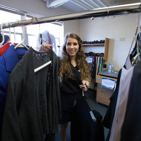 student volunteer working with clothing in Wildcat Wardrobe