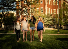 photo of 4 female students walking toward camera from Miller Hall