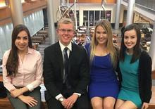 photo of Natalya Hippisley, Brennan Dodds, Haley Holthaus, Amy Keith - CatSwap Books in the Gatton Building with hanging sculpture, dining area behind them