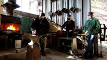 Photo of Jeremy Colbert forging a piece of metal while two other men watch