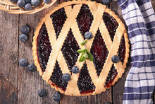 photo of blueberry pie with blueberries on top and to side