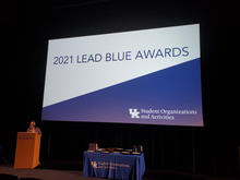 """Screen in auditorium reading """"2021 Lead Blue Awards"""" against white and blue background"""