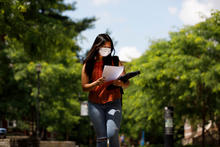 photo of student in mask walking on campus