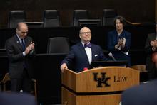 J. David Rosenberg standing behind podium in suit