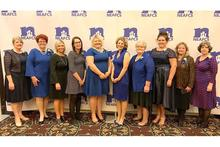 Portrait of UK Extension Agent representatives in formal attire with sponsored backdrop