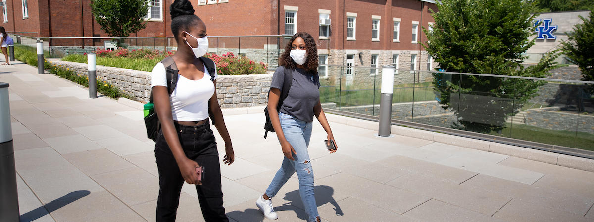Photo of two female students in COVID-19 protective masks walking on campus