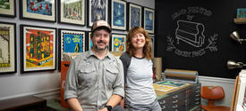Brian and Sara Turner at Cricket Press in front posters of their work