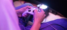 photo of young man's hands playing an egame.